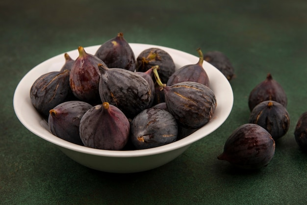 Top view of sweet black mission figs on a bowl on a green wall