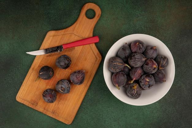Vista dall'alto di dolci fichi neri missione su una ciotola con fichi neri su una tavola da cucina in legno con coltello su una parete verde