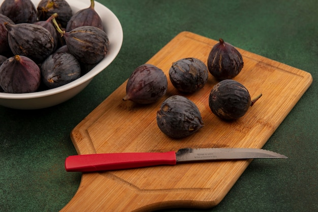 Top view of sweet black mission figs on a wooden kitchen board with knife on a green wall