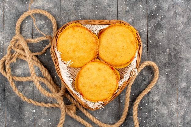 Вид сверху сладкие пирожные вокруг вкусной вкусной внутри корзины на сером полу