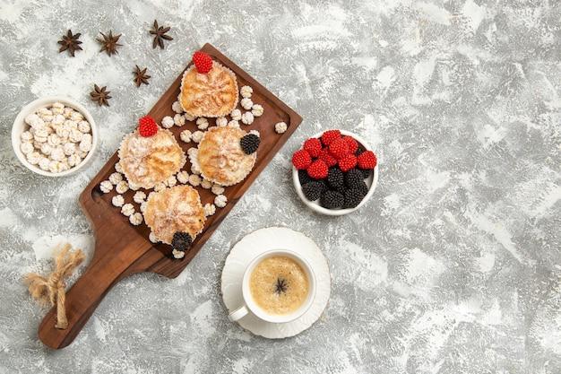 Вид сверху сладкие пирожные с конфетами и чашкой кофе на белом фоне