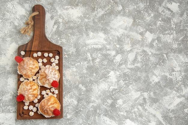 Vista dall'alto torte dolci con caramelle sulla scrivania bianca