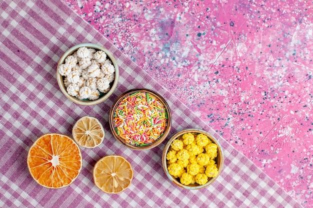 ピンクの机の上に甘いキャンディーのカラフルなコンフィチュール