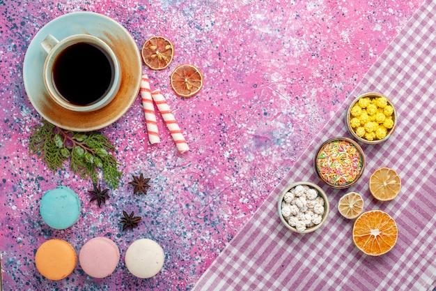 ピンクの机の上にお茶とマカロンとトップビューの甘いキャンディーカラフルなコンフィチュール
