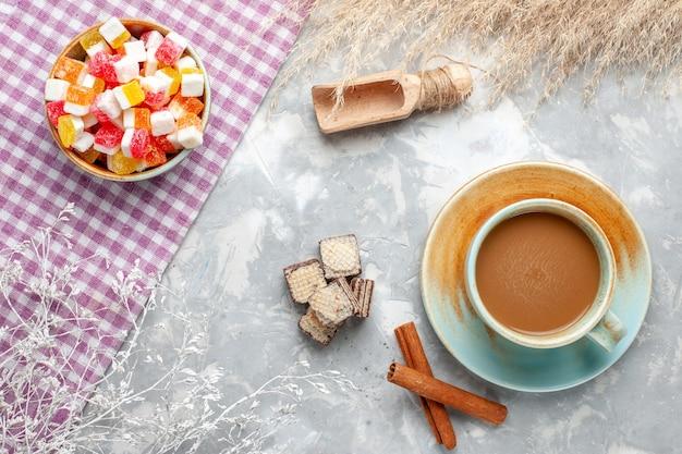 明るい背景の上のシナモンとミルクコーヒーと甘いキャンディーの上面図キャンディー甘い砂糖の写真の色