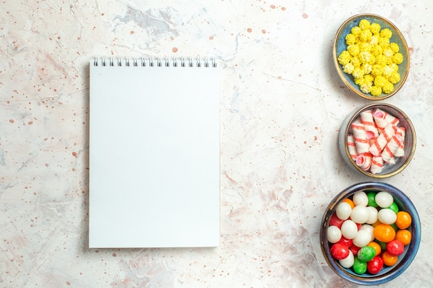 白いテーブルの上のconfituresが付いている上面図の甘いキャンディー虹色の砂糖菓子
