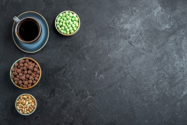 濃い灰色の背景にコーヒーカップと甘いキャンディーの上面図