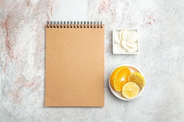 Caramelle dolci vista dall'alto con limone e blocco note sulla frutta biscotto caramelle tavolo bianco