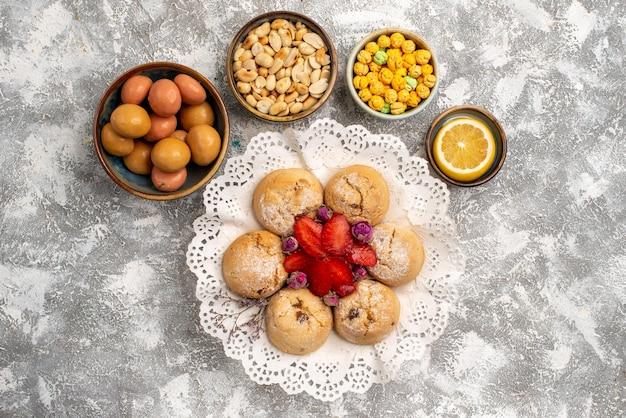 Vista dall'alto di caramelle dolci con biscotti alle noci sulla superficie bianca