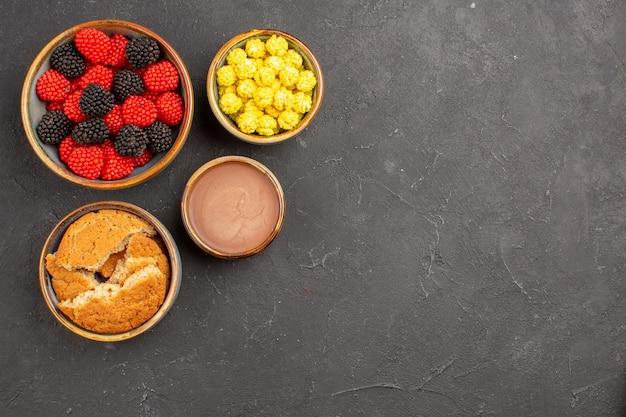 Vista dall'alto confetture di caramelle dolci su sfondo scuro color caramella al gusto di frutti di bosco tè