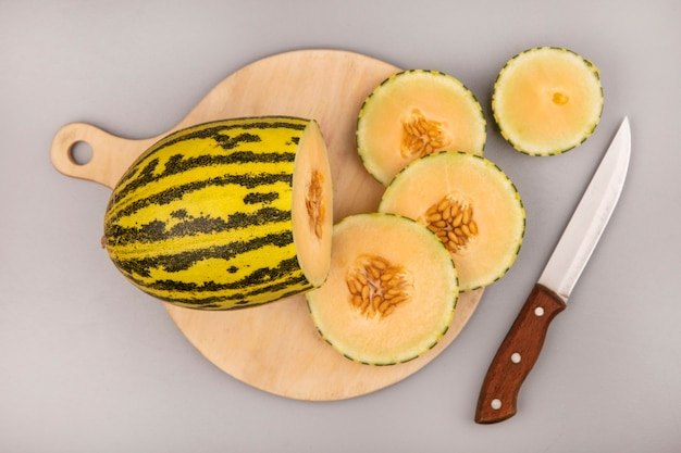 Top view of sweet cantaloupe melon with slices on a wooden kitchen board with knife on a white wall