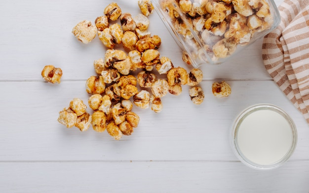 Top view of sweet caramel popcorn scattered from glass jar on white wooden table
