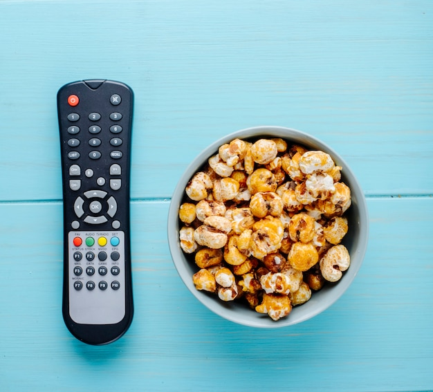Top view of sweet caramel popcorn with tv remote on blue background