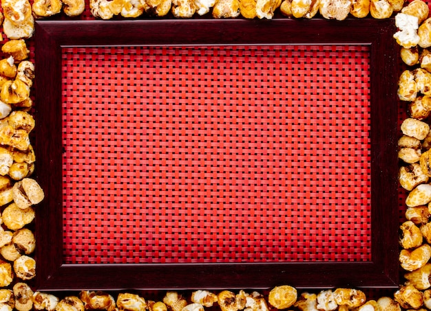 Top view of sweet caramelized pop corn scattered around the empty picture frame on red background with copy space