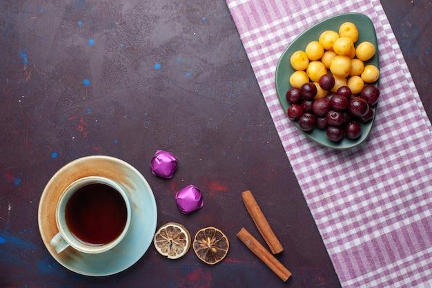 Vista dall'alto di ciliegie dolci insieme a cannella e tazza di tè sulla superficie scura