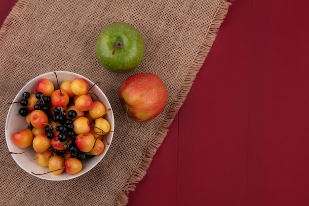 Top view of sweet cherry with black currants in a bowl with apples on a red surface