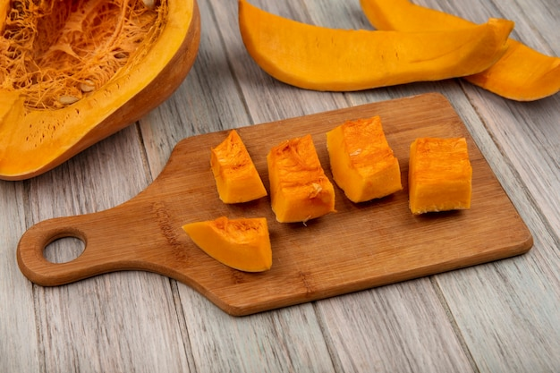 Vista dall'alto di fette di zucca tritate dolci su un tagliere di cucina in legno con bucce di zucca isolato su una superficie di legno grigia