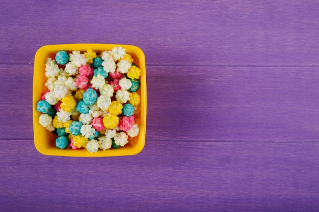 Top view of sweet colorful sugar candies in a bowl on purple wooden background with copy space