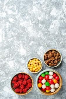 Vista dall'alto confitures dolci caramelle e noci su sfondo bianco zucchero biscotto tè dolce