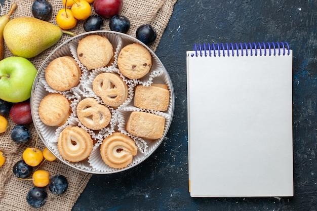 ダークブルーのデスクにさまざまな新鮮なフルーツのメモ帳と一緒にトップビューの甘いクッキーフルーツクッキービスケット甘い新鮮な
