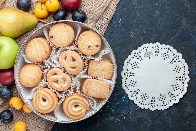 Vista dall'alto biscotti dolci insieme a diversi tipi di frutta fresca sul tavolo blu scuro biscotto alla frutta dolce fresco