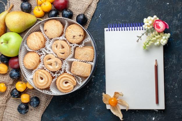 Вид сверху сладкое печенье вместе с различными свежими фруктами блокнот на темно-синем столе фруктовое печенье печенье сладкое свежее