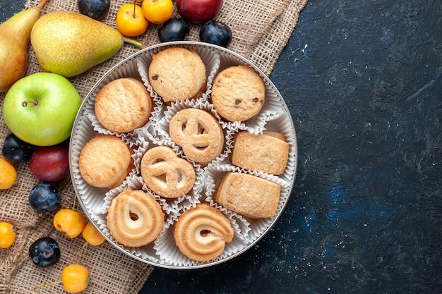 ダークブルーのデスクにさまざまな新鮮なフルーツと一緒にトップビューの甘いクッキーフルーツクッキービスケット甘い新鮮な
