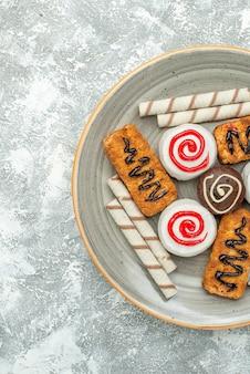 상위 뷰 달콤한 쿠키와 밝은 흰색 배경에 케이크 케이크 비스킷 차 설탕 쿠키 달콤한