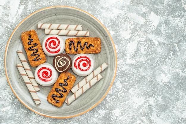 상위 뷰 달콤한 쿠키와 케이크 흰색 배경에 케이크 비스킷 차 설탕 쿠키 달콤한