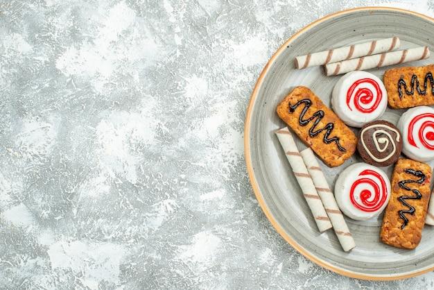 Вид сверху сладкое печенье и пирожные на белом фоне торт бисквитный чай сахарное печенье сладкое