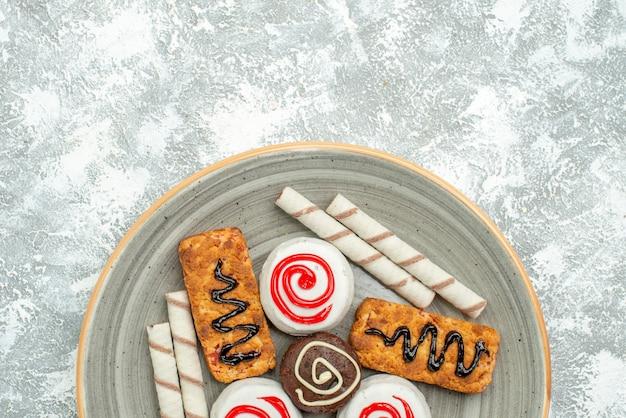 Top view sweet cookies and cakes on white floor cake biscuit tea sugar cookie sweet