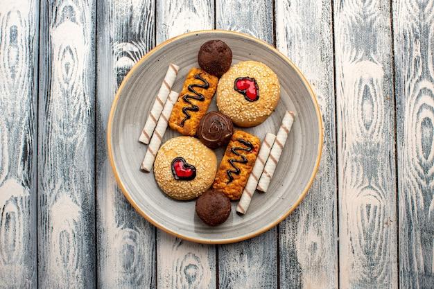 Вид сверху сладкое печенье вкусные сладости внутри тарелки на сером деревенском фоне чайное печенье бисквитное сахарное сладкое