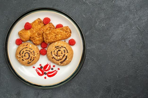 Vista dall'alto biscotti dolci deliziosi dolci per il tè sulla torta di biscotto dolce zucchero biscotto scrivania grigia