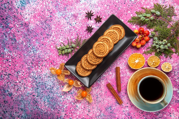 Top view of sweet cookies inside black form with cup of tea and cinnamon on light pink surface