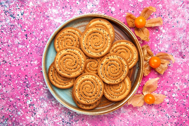 Top view of sweet cookies inside plate on pink surface