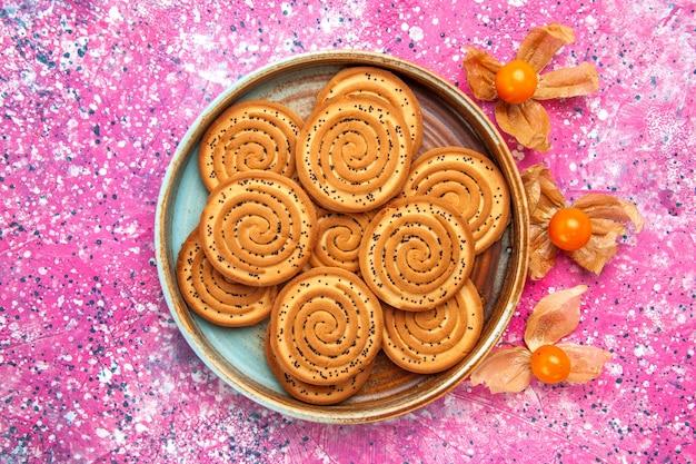Vista dall'alto di biscotti dolci all'interno della piastra sulla superficie rosa