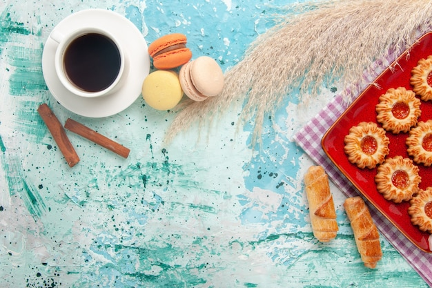 Вид сверху сладкое печенье с бубликами, макаронами и чашкой чая на голубом фоне