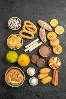 灰色の背景にビスケットとキャンディーと甘いクッキーの上面図