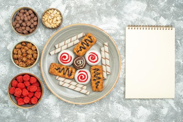 上面図白い背景の上のケーキとキャンディーと甘いクッキービスケット甘いクッキーシュガーケーキティー
