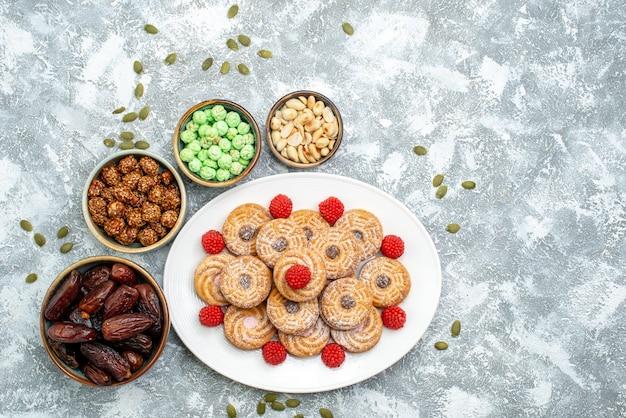上面図白い背景の上のキャンディーとコンフィチュールの甘いクッキーシュガービスケットティー甘いケーキ