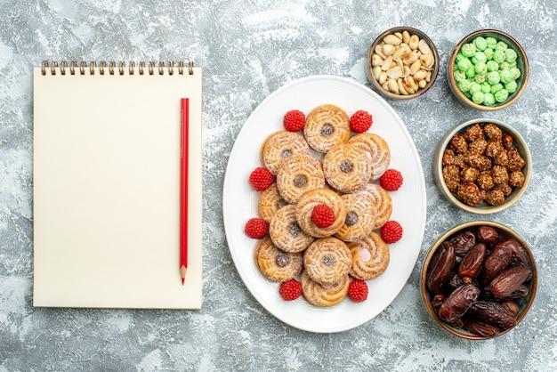 ライトホワイトの背景にキャンディーとコンフィチュールが付いた上面の甘いクッキーシュガービスケットティーの甘いケーキ
