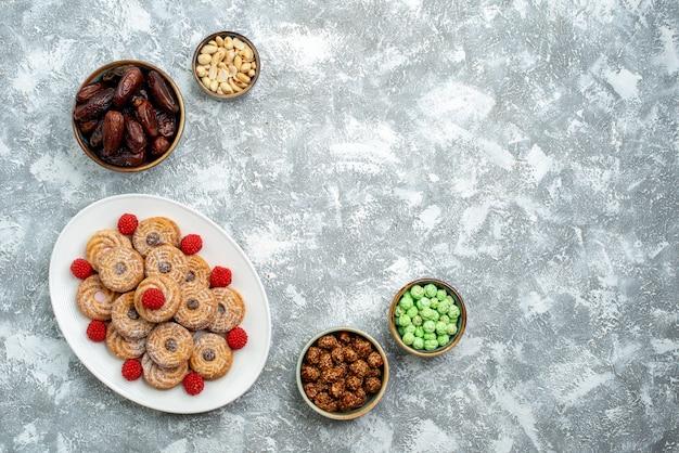 Вид сверху сладкое печенье с конфетами и конфитюрами на белом фоне печенье сахар бисквит торт чай сладкий