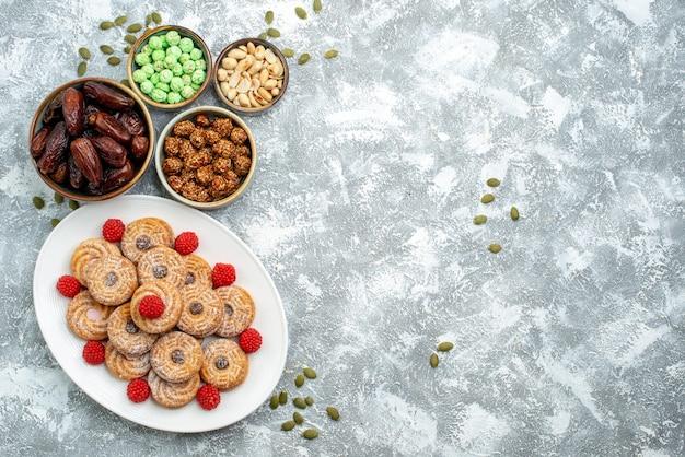 Вид сверху сладкое печенье с конфетами и конфитюрами на белом столе, печенье, сахар, бисквит, торт, сладкий