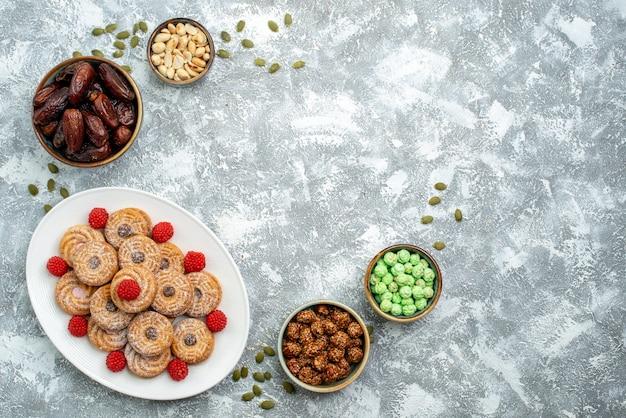 Vista dall'alto biscotti dolci con caramelle e confitures su sfondo bianco biscotto zucchero biscotto torta tè dolce