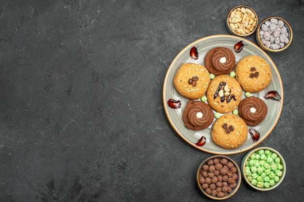 Top view sweet cookies with candies on dark-grey background sugar cookie sweet biscuit cake tea