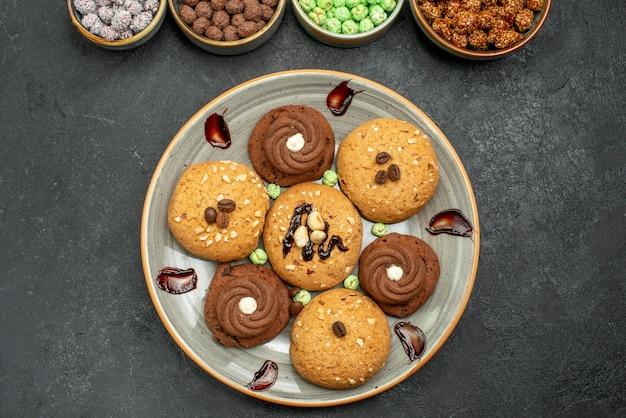 Вид сверху сладкое печенье с конфетами на сером фоне сахарное печенье сладкий бисквитный торт чай