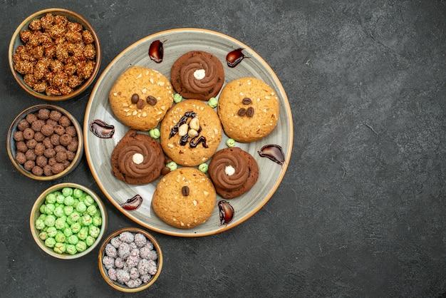 회색 책상에 사탕과 상위 뷰 달콤한 쿠키 설탕 쿠키 달콤한 비스킷 케이크 차