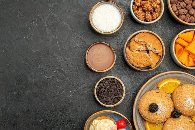 暗い表面にチップとオレンジスライスが付いた上面の甘いクッキーフルーティクッキービスケット甘いパイケーキ