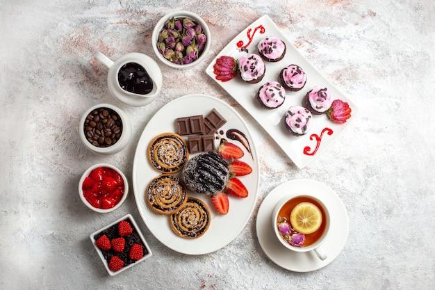 白い背景の上のチョコレートケーキとお茶とトップビューの甘いクッキークッキービスケットシュガーティー甘いケーキ