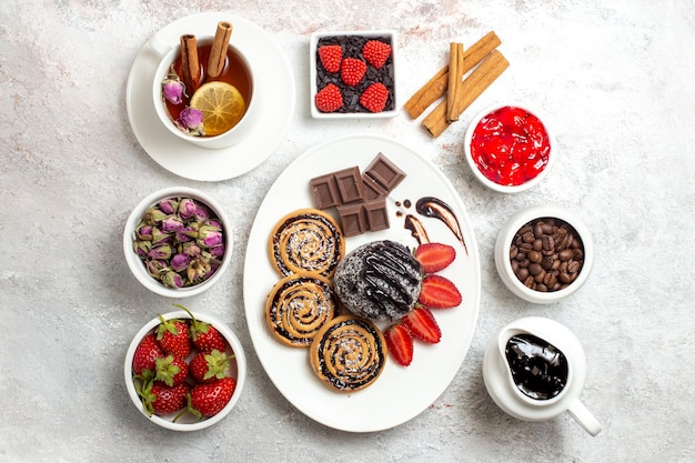 白い背景の上のチョコレートケーキとお茶とトップビューの甘いクッキー甘いビスケットシュガーケーキクッキー